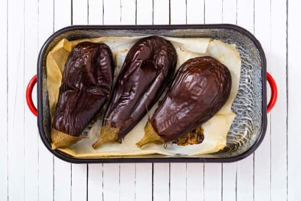 3 baked eggplants in a roasting pan