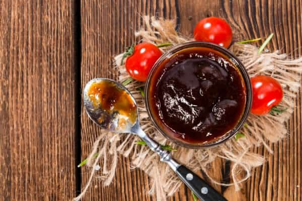 bowl of barbecue sauce with cherry tomatoes on table