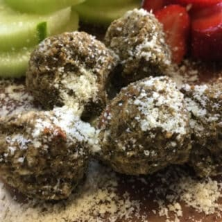 eggplant meatballs sprinkled with parmsean cheese on a plate with cucumbers and strawberries
