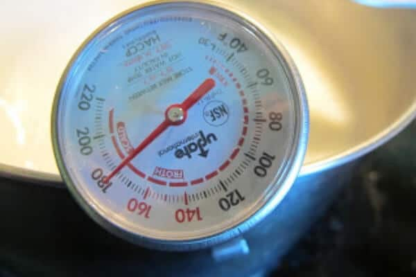 thermometer clipped to the side of a pot of fresh goat milk