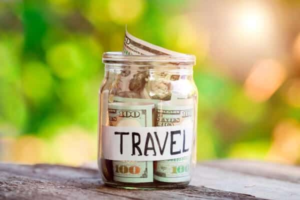 jar of money labeled travel on a table