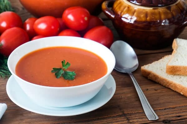 tomato soup in white bowl on a table with spoon