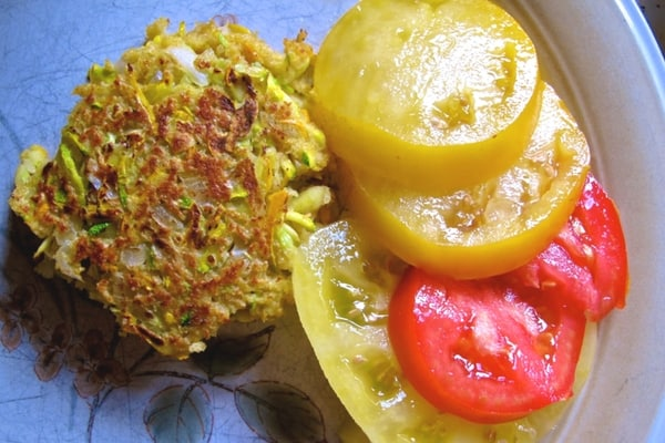 poor man's zucchini crab cake on a plate with sliced yellow and red tomatoes